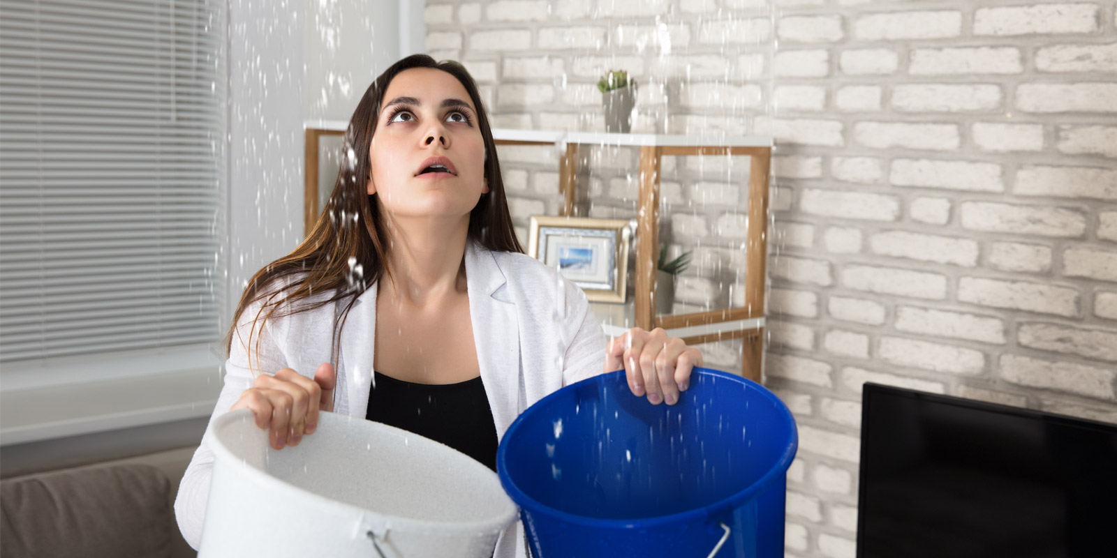 a woman holding two buckets under a burst pipe while she waits for a water mitigation company to arrive